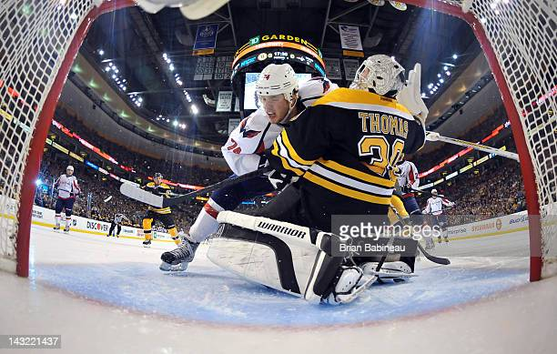 John Carlson of the Washington Capitals collides into Tim Thomas of the Boston Bruins in Game Five of the Eastern Conference Quarterfinals during the...