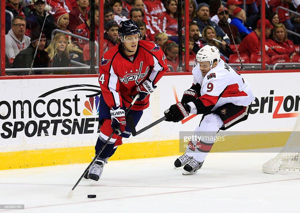 John Carlson #74 of the Washington Capitals moves the puck past Milan Michalek #9 of the Ottawa Senators during the second half at Verizon Center on November 27, 2013 in Washington, DC.