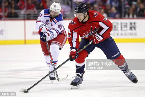 John Carlson of the Washington Capitals skates past Rick Nash of the New York Rangers during the second period at Capital One Arena on December 08...