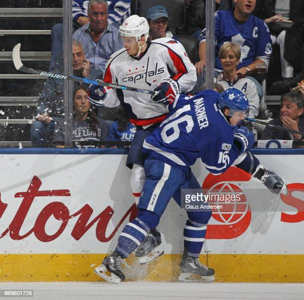 John Carlson of the Washington Capitals takes a hit from Mitchell Marner of the Toronto Maple Leafs in Game Three of the Eastern Conference...