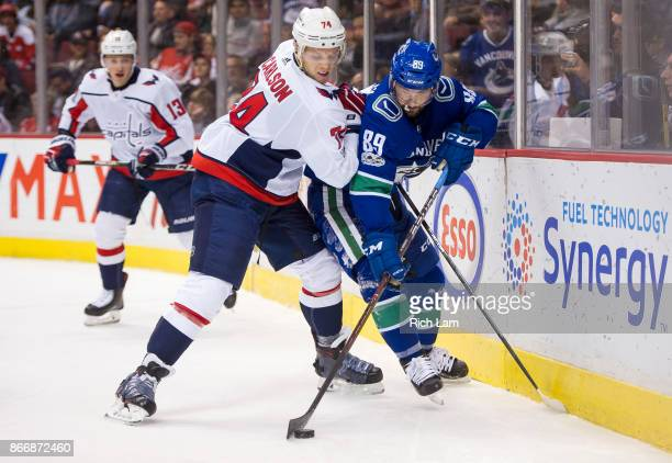 John Carlson of the Washington Capitals tries to check Sam Gagner of the Vancouver Canucks off the puck in NHL action on October 2017 at Rogers Arena...
