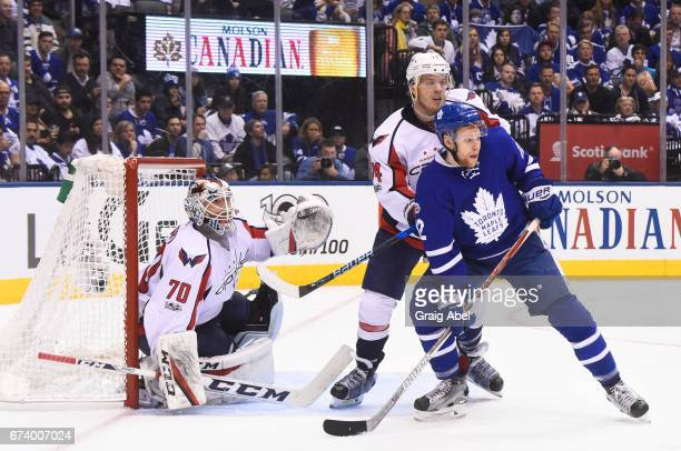 John Carlson of the Washington Capitals tries to clear Connor Brown of the Toronto Maple Leafs from the front of the net of Braden Holtby of the...