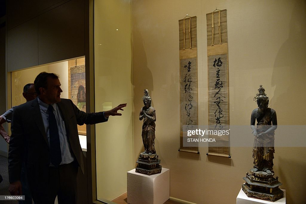 John Carpenter, (L), Curator of Japanese Art, Department of Asian Art, describes two hanging scrolls, 'Buddhist Maxim' by Gukyoku Reisai, 15th century, on display in the exhibition 'Brush Writing in the Arts of Japan' August 19, 2013 at The Metropolitan Museum of Art in New York. The wood statues with gold paint and gold leaf are 'Seishi Bosatsu' (L) and 'Kannon Bosatsu' (R) from the Kamakura period, 12th - 13th century. AFP PHOTO/Stan HONDA