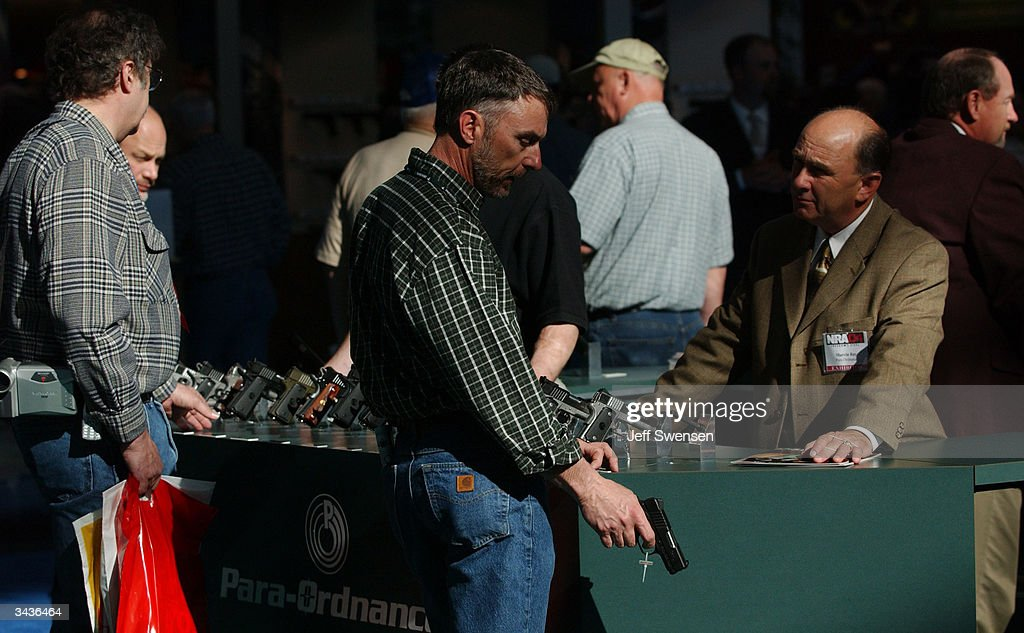 John Cash of Indiana inspects a 45 caliber semiautomatic pistol on display at the 133rd National Rifle Association National Convention at the David L...