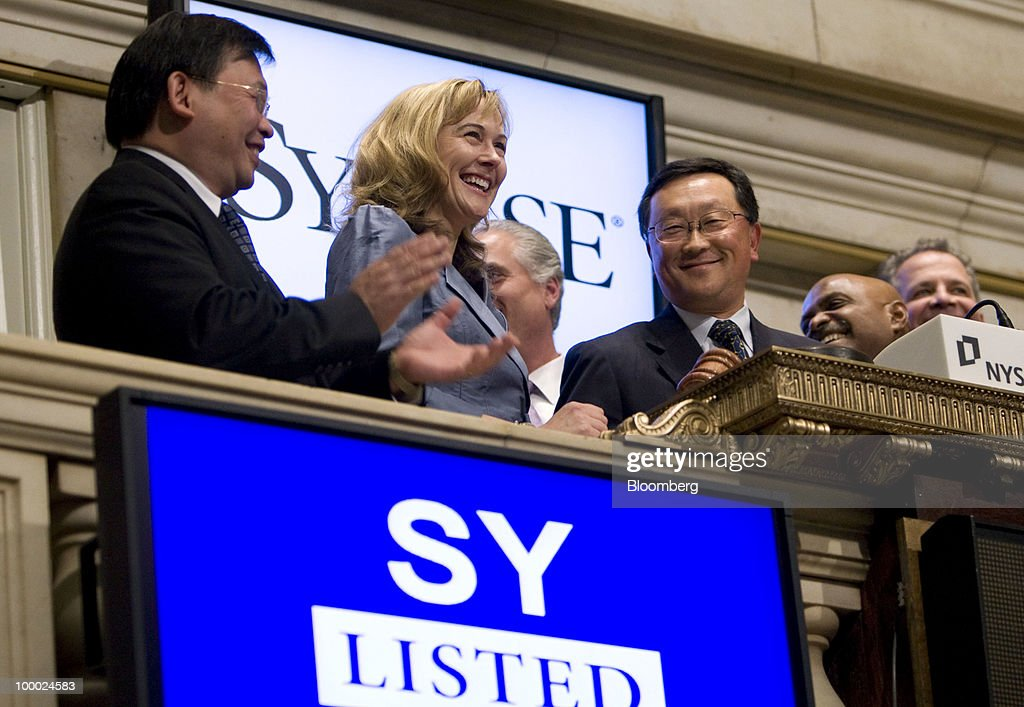 John Chen, chairman, chief executive officer and president of Sybase Inc., center right, rings the closing bell at the New York Stock Exchange in New York, U.S., on Thursday, May 20, 2010. Chen said in an interview with CNBC that he thinks the deal with SAP AG will 'get done.' Photographer: Jin Lee/Bloomberg via Getty Images