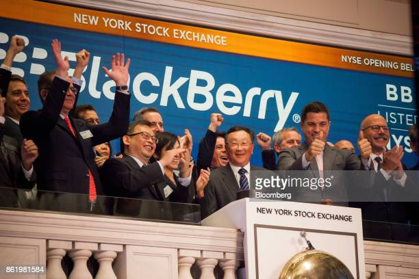 John Chen executive chairman and chief executive officer of BlackBerry Ltd center rings the opening bell during the company's listing migration to...