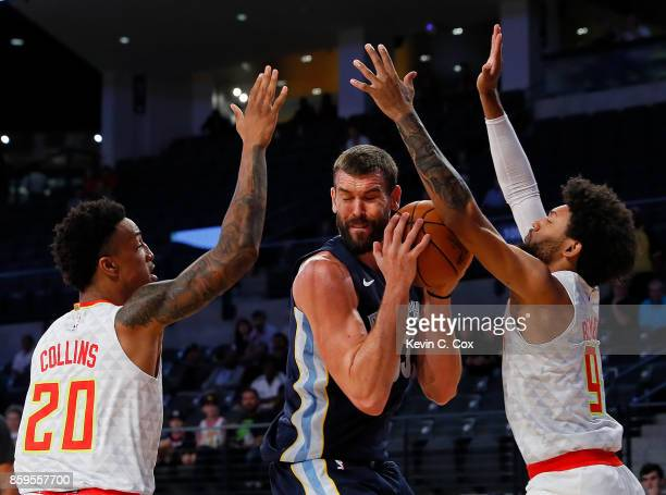 John Collins and DeAndre' Bembry of the Atlanta Hawks trap Marc Gasol of the Memphis Grizzlies at McCamish Pavilion on October 9 2017 in Atlanta...