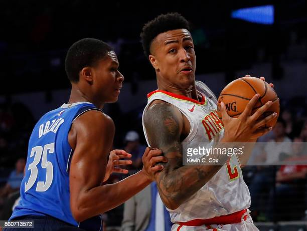 John Collins of the Atlanta Hawks drives against PJ Dozier of the Dallas Mavericks at McCamish Pavilion on October 12 2017 in Atlanta Georgia NOTE TO...