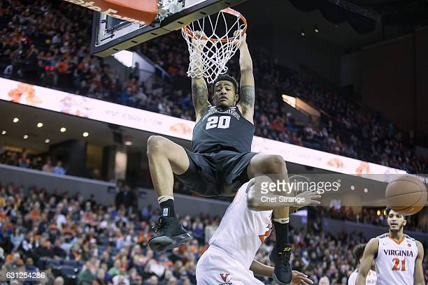 John Collins of the Wake Forest Demon Deacons dunks the ball over Mamadi Diakite of the Virginia Cavaliers at John Paul Jones Arena on January 8 2017...