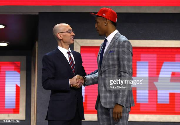 John Collins walks on stage with NBA commissioner Adam Silver after being drafted 19th overall by the Atlanta Hawks during the first round of the...