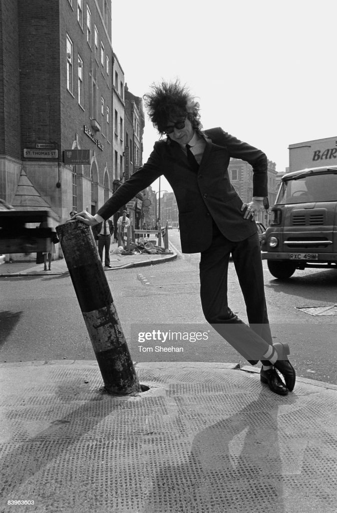 John Cooper Clarke leant against a street bollard, London, circa 1977.