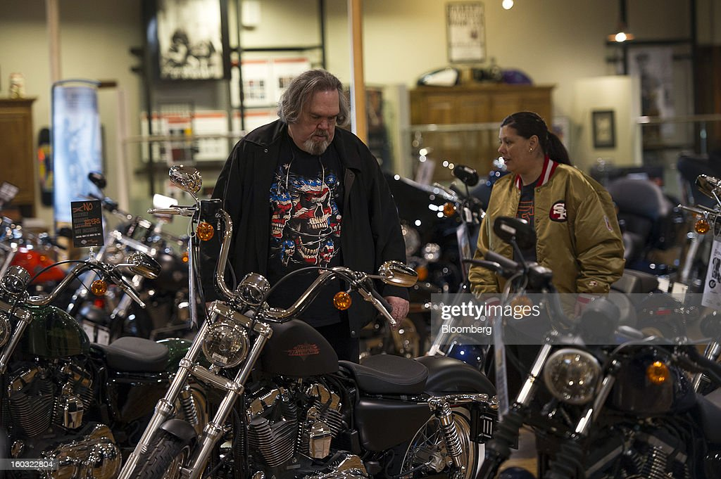 John Craig, left, and Laura Craig look at Harley-Davidson Inc. motorcycles on the showroom floor at the Dudley Perkins Co. dealership in South San Francisco, California, U.S., on Monday, Jan. 28, 2013. Harley-Davidson reported fourth quarter revenue of $1.17 billion. Photographer: David Paul Morris/Bloomberg via Getty Images
