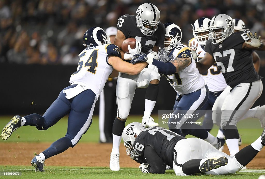 John Crockett #43 of the Oakland Raiders gets tackled by Bryce Hager #54 and Morgan Fox #97 of the Los Angeles Rams during the third quarter of their preseason NFL football game at Oakland-Alameda County Coliseum on August 19, 2017 in Oakland, California. The Rams won the game 24-21.