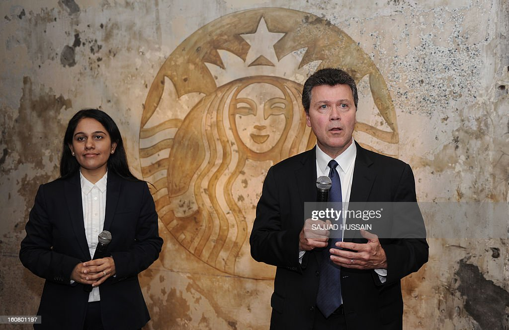 John Culver, president of Starbucks China and Asia Pacific, addresses journalists while chief executive officer of India's Tata Starbucks limited Avani Saglani Davda looks on at the newly-inaugurated Starbucks outlet in New Delhi on February 6, 2013. Starbucks, the world's biggest coffee chain, launched its first outlet in New Delhi on Wednesday with an aim to expand its reach to customers across India.