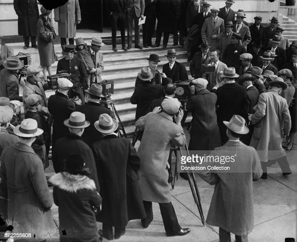 John D Rockefeller Jr facing a battery of cameramen at the Capitol in Washington today after testifying before the Senate Public Lands Committee...