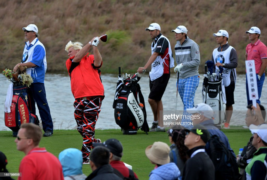 John Daly both of the US tees off watched by playing partners Peter Uihlein (3rd R) and Luke Guthrie (R) both of the US at the 9th hole during day two of the BMW Shanghai Masters golf tournament at the Lake Malaren Golf Club in Shanghai on October 25, 2013. The 7 million USD event is being held for the second time at the Lake Malaren Golf Club. AFP PHOTO/Mark RALSTON