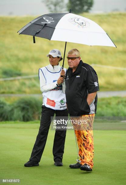 John Daly of the United States and his caddie and wife Anna Cladakis shelter from the rain during day two of the DD REAL Czech Masters at Albatross...