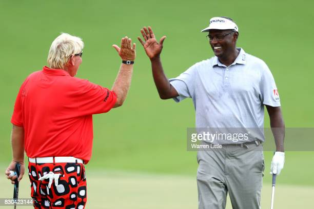 John Daly of the United States and Vijay Singh of Fiji highfive each other after making birdie putts on the 18th hole during the second round of the...