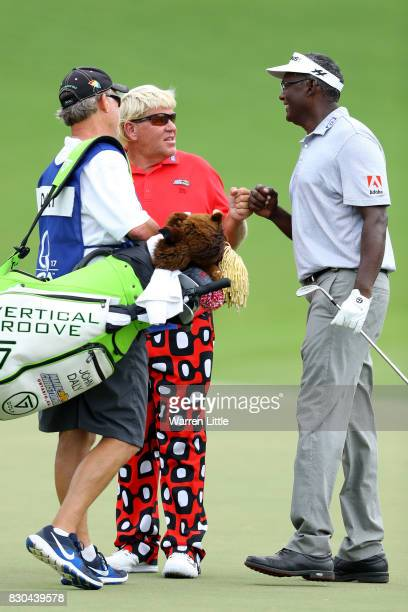 John Daly of the United States congratulates Vijay Singh of Fiji after chipping in for birdie on the 18th hole during the second round of the 2017...