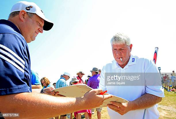 John Daly of the United States signs an autograph for a fan during a practice round prior to the 2015 PGA Championship at Whistling Straits on August...