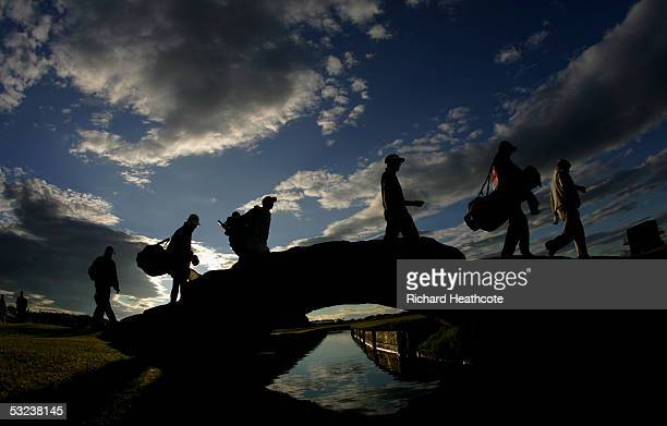 John Daly of the USA and Stuart Appleby of Australia cross the Swilken Bridge with caddies during the first round of the 134th Open Championship at...