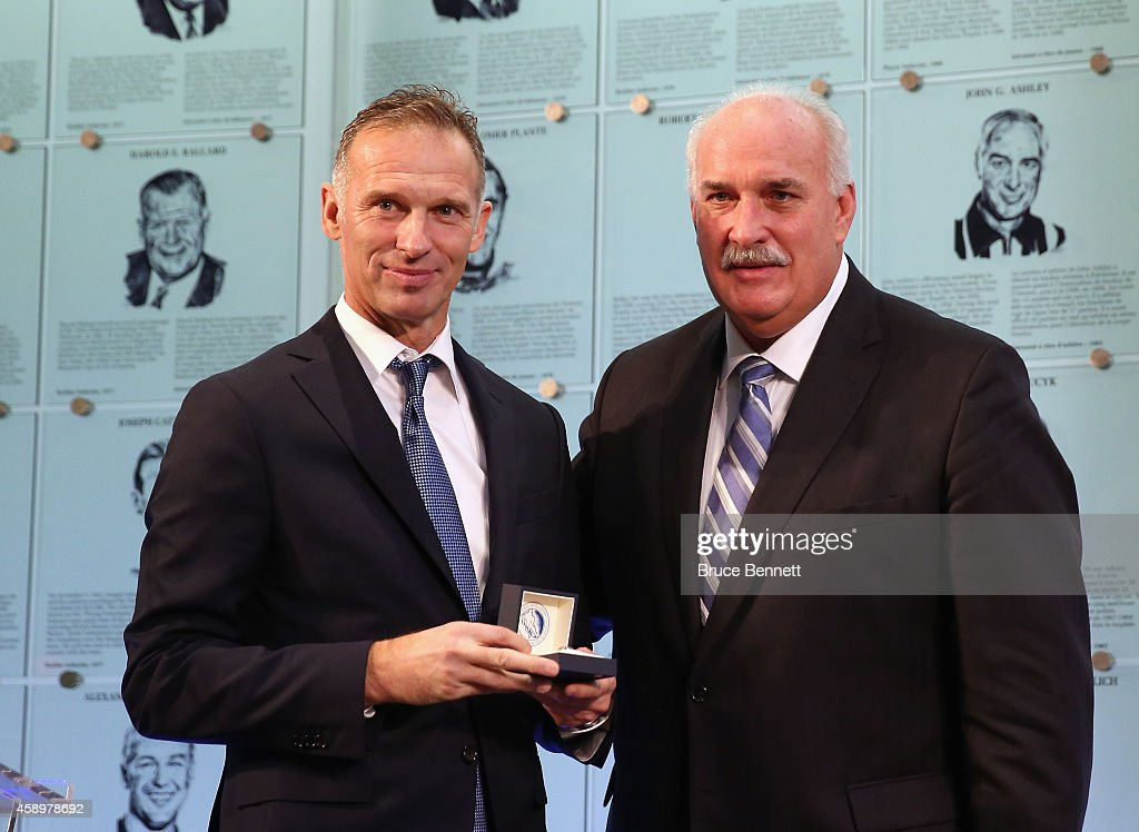 John Davidson Chairman of the Hockey Hall of Fame Selection Committee presents the Hall of Fame ring to 2014 inductee Dominik Hasek during a photo...