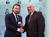 John Davidson Chairman of the Hockey Hall of Fame Selection Committee presents the Hall of Fame ring to 2014 inductee Peter Forsberg during a photo...