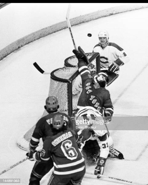 John Davidson of the New York Rangers attempts to knock the puck out of the air and away from the net during a game against the Montreal Canadiens...