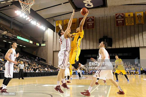 John Davis of the Towson Tigers drives to basket over Ryder Bowline of the Elon Phoenix during the first round of the CAA Basketball Tournament at...