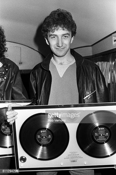John Deacon of Queen holding up a gold disc on board a train from Leiden to Amsterdam Netherlands after a gig at Groenoordhal Leiden 25th April 1982