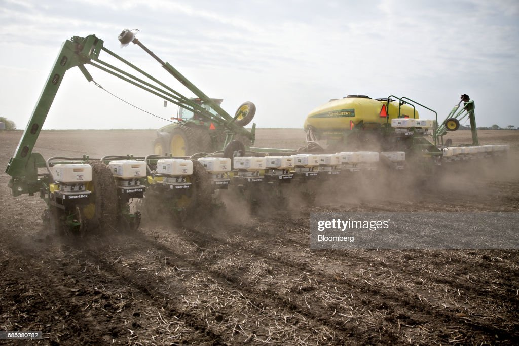 A John Deer & Co. tractor pulls a planter while distributing non-GMO corn seed on a field in Malden, Illinois, U.S., on Wednesday, May 17, 2017. Rain in the Midwest and Great Plains will slow corn, soybean and wheat planting progress as well as curb seed germination and early growth, according to a senior meteorologist at the MDA Weather Services. Photographer: Daniel Acker/Bloomberg via Getty Images