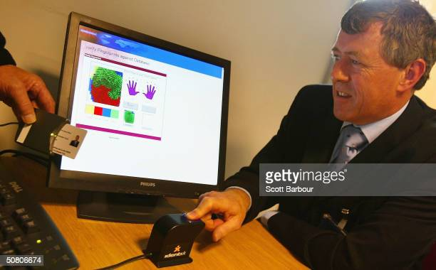 John Denham the chairman of Britain's Home Affairs Select Committee looks at a computer screen displaying information after he has his fingerprint...