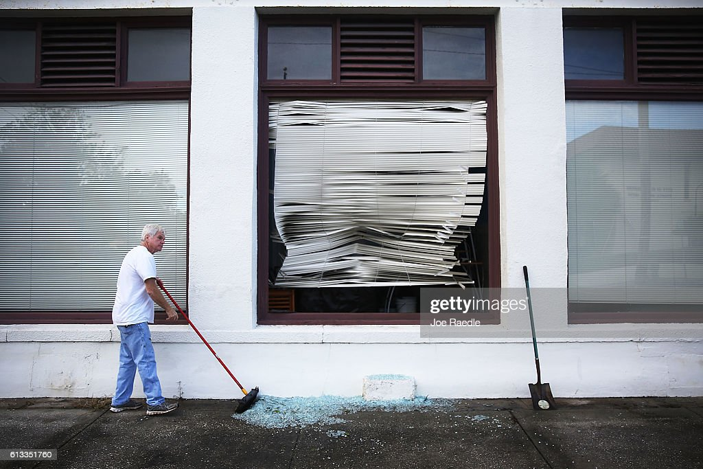 John Dennehy cleans up broken glass after a window was broken when Hurricane Matthew passed through the area on October 8 2016 in St Augustine...
