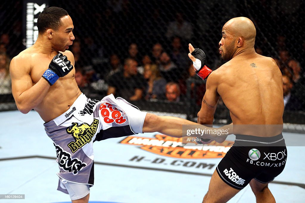 John Dodson (L) kicks Demetrious Johnson (R) during thier Flyweight Championship Bout part of UFC on FOX at United Center on January 26, 2013 in Chicago, Illinois.