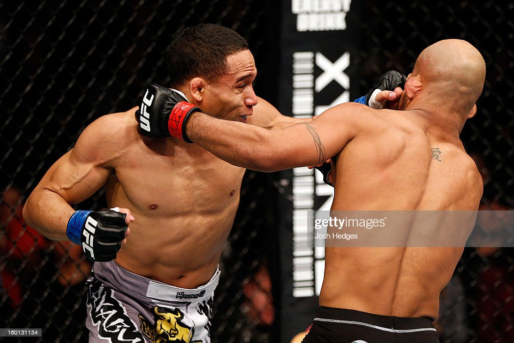 John Dodson (L) punches Demetrious Johnson (R) during thier Flyweight Championship Bout part of UFC on FOX at United Center on January 26, 2013 in Chicago, Illinois.