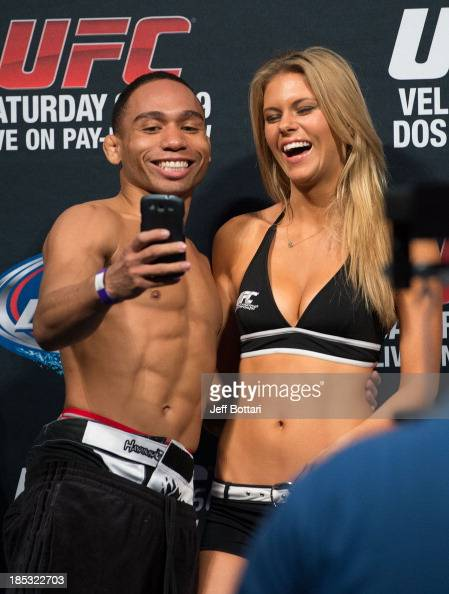 John Dodson takes a picture with UFC Octagon Girl Chrissy Blair on stage during the UFC 166 weighin at the Toyota Center on October 18 2013 in...