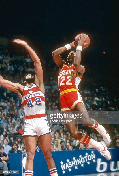 John Drew of the Atlanta Hawks shoots over Greg Ballard of the Washington Bullets during an NBA basketball game circa 1980 at The Capital Centre in...