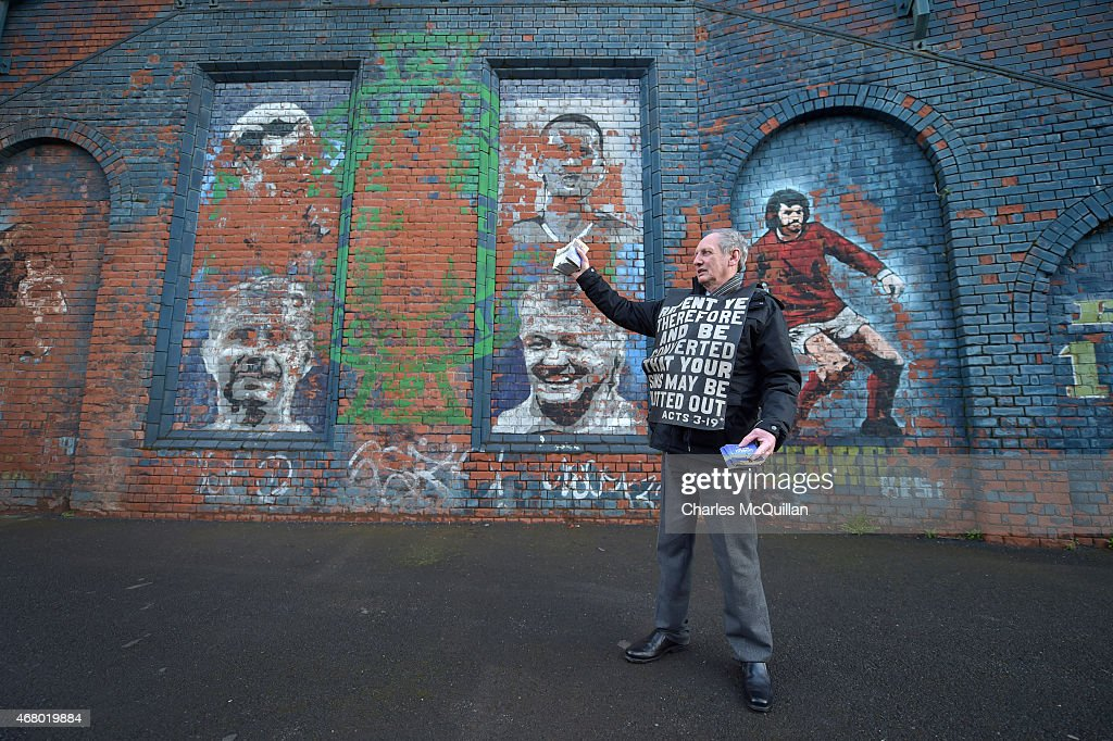 John Dumigan hands out religious tracts against the backdrop of a George Best mural as the Evangelical Protestant Society hold a protest against football on a Sunday before the EURO 2016 Group F qualifier between Northern Ireland and Finland at Windsor Park on March 29, 2015 in Belfast, Northern Ireland. Todays game is the first professional game to take place on a Sunday in Northern Ireland.