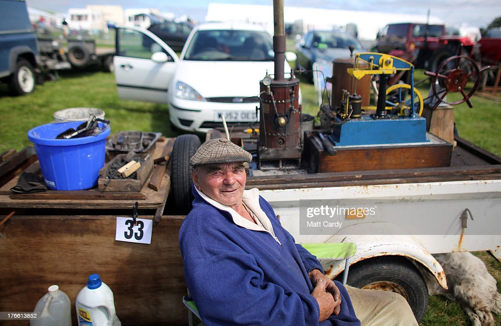 John Edwards sits besides his stationary beam engine his showing at the Cornish Steam and Country Fair at the Stithians Showground on August 16, 2013 near Penryn, England. The annual show, now in 58th year, is one of Cornwall's largest outdoor events and is one of the UK's most popular and respected steam rallies.