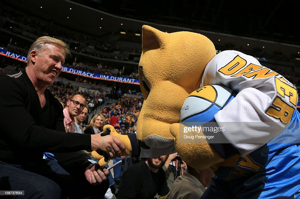 John Elway, Executive Vice President of Football Operations for the Denver Broncos autographs a basketball for Rocky, the mascot of the Denver Nuggets, as the Nuggets host the Los Angeles Lakers at Pepsi Center on December 26, 2012 in Denver, Colorado. The Nuggets defeated the Lakers 126-114.