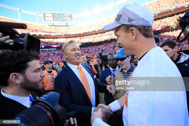 John Elway executive vice president of football operations for the Denver Broncos celebrates with Peyton Manning after they defeated the New England...