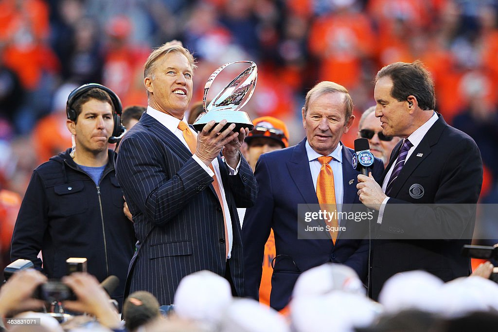 John Elway executive vice president of football operations for the Denver Broncos celebrates with the Lamar Hunt Trophy after they defeated the New...