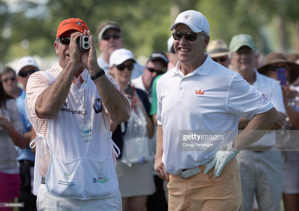John Elway observes as his caddie George Solich measures the distance to the green as Elway prepares to take his second shot on the second hole...