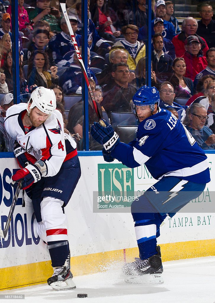John Erskine #4 of the Washington Capitals battles for control of the puck with Vincent Lecavalier #4 of the Tampa Bay Lightning during the first period of the game at the Tampa Bay Times Forum on February 14, 2013 in Tampa, Florida.