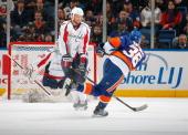 John Erskine of the Washington Capitals blocks a shot by Travis Hamonic of the New York Islanders on January 20 2011 at Nassau Coliseum in Uniondale...