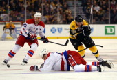 John Erskine of the Washington Capitals deflects the puck from Kevan Miller of the Boston Bruins during a game at the TD Garden on March 1 2014 in...
