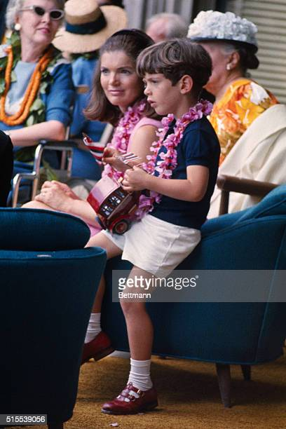 John F Kennedy is pictured with his mother and others as they watch the annual Kamehameha Day Parade from the office balcony of Governor John Burns...