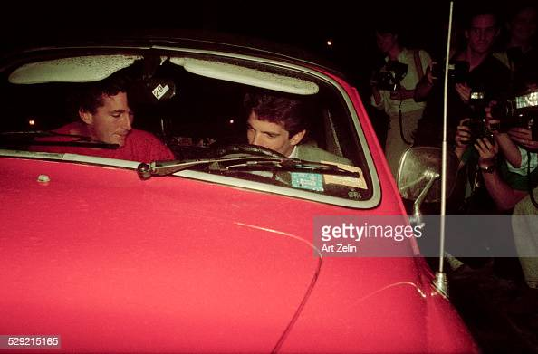 John F Kennedy Jr in sports car with a friend Photographers on the left circa 1970 New York
