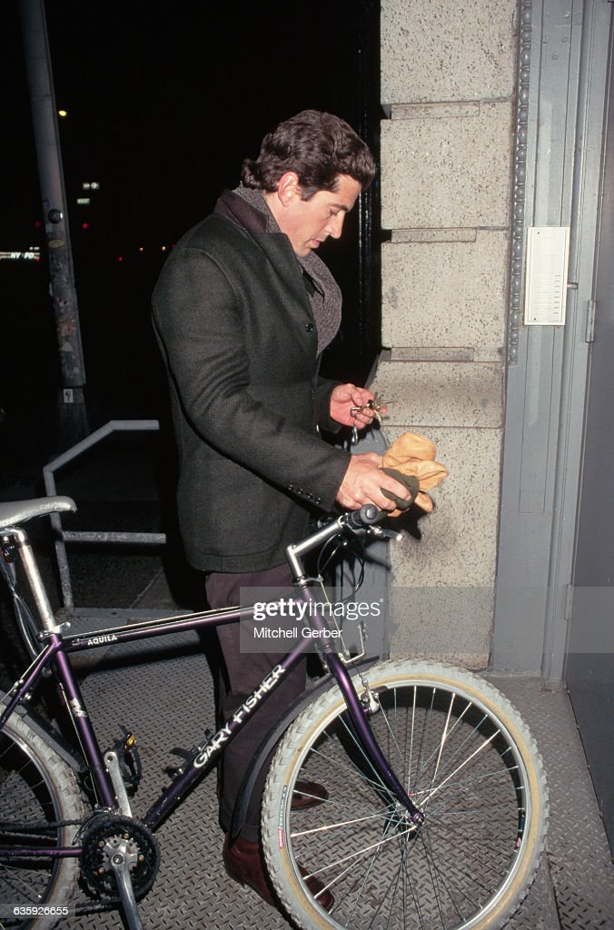 John F. Kennedy Jr. stand with his bicycle as he prepares to unlock