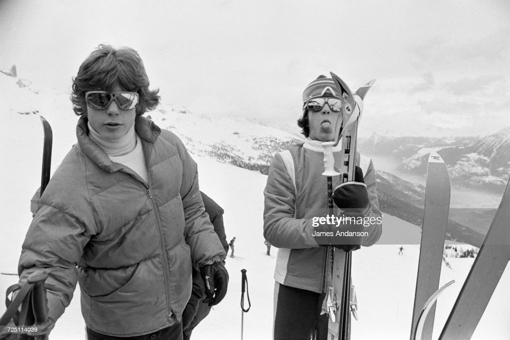 John F. Kennedy Jr. (1960 - 1999, right) sticking out his tongue, during a holiday at the Crans-sur-Sierre ski resort in Switzerland, 27th December 1974.